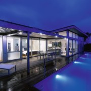 Night view of house and pool area with apartment, architecture, condominium, daylighting, estate, home, house, lighting, property, real estate, reflection, residential area, sky, swimming pool, window, blue