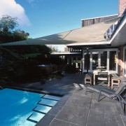 Pool area with large grey pavers, outdoor furniture, architecture, estate, home, house, outdoor structure, property, real estate, reflection, roof, shade, sky, swimming pool, water, black, teal
