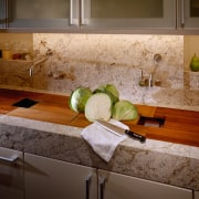 View of the countertop & faucets - View countertop, floor, flooring, granite, interior design, kitchen, room, sink, table, tile, under cabinet lighting, wood, brown
