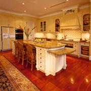 View of the kitchen area - View of cabinetry, countertop, cuisine classique, floor, flooring, furniture, hardwood, interior design, kitchen, laminate flooring, room, wood, wood flooring, orange, red