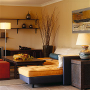 View of the living area - View of floor, flooring, furniture, home, interior design, living room, room, table, brown, orange