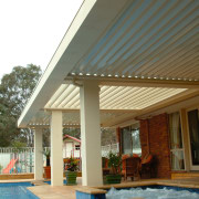 Outdoor living space showing vergola and water feature awning, daylighting, outdoor structure, property, real estate, roof, shade, swimming pool, brown