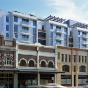 Apartment complex behind a row of heritage buildings. apartment, building, city, commercial building, condominium, downtown, facade, hotel, metropolitan area, mixed use, neighbourhood, property, real estate, residential area, window