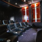 black leather coaches, dark blue carpet, wooden wall interior design, black