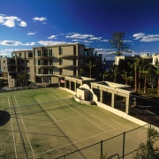 exterior view of tenis courts - exterior view apartment, architecture, building, campus, city, condominium, corporate headquarters, estate, mixed use, neighbourhood, property, real estate, residential area, roof, sky, structure, suburb, urban area, urban design, brown, black, blue