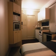 Compact studio accommodation in neutral colours with bed, countertop, home appliance, interior design, kitchen, room, brown