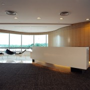Office reception area with cream front desk, wood architecture, ceiling, daylighting, floor, flooring, furniture, glass, interior design, lobby, table, gray, black