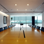 Office boardroom with large wood table and black ceiling, conference hall, daylighting, floor, flooring, interior design, real estate, table, gray, brown