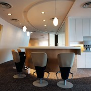 Office breakout area with stool chairs at curved ceiling, conference hall, furniture, interior design, light fixture, lighting, lobby, product design, table, gray