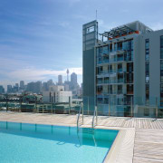 Rooftop swimming pool with timber decking and another apartment, architecture, building, city, condominium, corporate headquarters, daytime, estate, hotel, metropolitan area, mixed use, property, real estate, residential area, sea, sky, swimming pool, tower block, water, teal