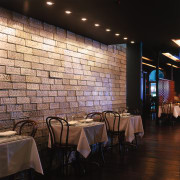 Restaurant with tables and chairs along feature wall ceiling, interior design, lighting, restaurant, table, wall, black