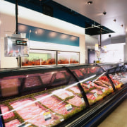 Covered food display cabinet in shop with blue food, meat, gray