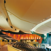 Auditorium with tiered seating and orange wall panels. architecture, auditorium, ceiling, daylighting, interior design, performing arts center, brown
