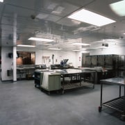 Commercial kitchen with stainless steel equipment and grey factory, floor, gray