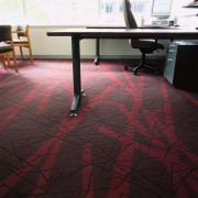 Textured carpet with red pattern in office with carpet, chair, floor, flooring, furniture, hardwood, laminate flooring, table, tile, wood, wood flooring, wood stain, black