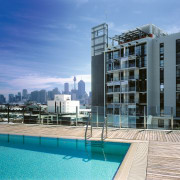 Rooftop swimming pool with timber decking, and glass apartment, architecture, building, condominium, estate, home, hotel, mixed use, property, real estate, residential area, sky, swimming pool, water, teal