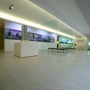 Showroom area with cream stone floor tiles, low exhibition, floor, interior design, lobby, real estate, tourist attraction, gray