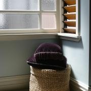 Old woven laundry basket in corner of room flooring, furniture, interior design, product design, window, gray