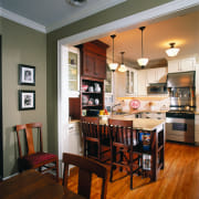View of the kitchen and dining areas, green cabinetry, countertop, dining room, furniture, hardwood, home, interior design, kitchen, living room, room, table, brown