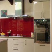 Kitchen with cream cabinetry, red splashback and stainless cabinetry, countertop, cuisine classique, furniture, home appliance, interior design, kitchen, kitchen stove, room, brown, orange