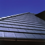 Close-up of roof showing grey shingle tiles and angle, architecture, building, cloud, daylighting, daytime, facade, landmark, line, roof, sky, sunlight, blue, black
