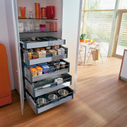A view of a kitchen area, wooden flooring, drawer, floor, furniture, product, shelf, shelving, white