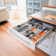 A view of a kitchen area, wooden flooring, countertop, drawer, floor, furniture, kitchen, product design, table, white, gray