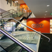 View of the steps to offices above, tiled architecture, escalator, glass, handrail, interior design, gray