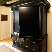 View of a black cabinetry unit, wooden flooring, cabinetry, furniture, black, orange