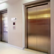 view of the large elevator form eastern elevators door, elevator, interior design, property, gray, brown