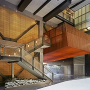 A view of the large metal rusty coloured architecture, building, daylighting, facade, stairs, wood, brown