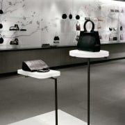 view of the hadbag displays offset against a black and white, chair, exhibition, floor, flooring, furniture, interior design, product design, table, gray, black