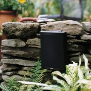 view of the outdoor voyager series speakers by grass, black