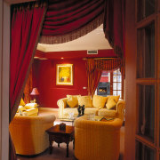 A view of a lounge area, brown carpet, ceiling, curtain, home, interior design, living room, room, suite, textile, window, window covering, window treatment, red, brown