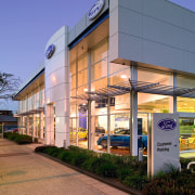 view of the ford showroom with  double architecture, building, commercial building, corporate headquarters, facade, mixed use, real estate, blue
