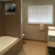 A view of a bathroom, brown tiled floor bathroom, floor, home, interior design, property, room, sink, tile, window, brown