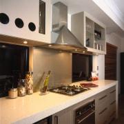 A view of a kitchen, wooden flooring, cream countertop, cuisine classique, interior design, kitchen, room, under cabinet lighting, gray, black