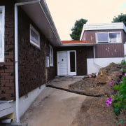 A view of the entrance way before the architecture, backyard, cottage, facade, home, house, property, real estate, residential area, roof, siding, window, yard, black, gray