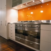 A view of a kitchen, wooden flooring, orange cabinetry, countertop, cuisine classique, home appliance, interior design, kitchen, kitchen stove, major appliance, room, under cabinet lighting, gray