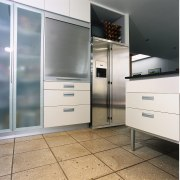 A view of a kitchen area, grey tiled cabinetry, floor, furniture, home appliance, white, gray