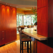 A view of the kitchen area, wooden cabinetry, architecture, ceiling, dining room, floor, flooring, furniture, hardwood, interior design, room, table, wall, window, wood, red, brown