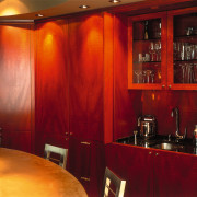 A view of a kitchen, wooden cabinetry and interior design, lighting, room, table, red