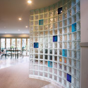 view of this glass block wall featuring solaris architecture, ceiling, daylighting, floor, flooring, glass, interior design, lobby, tile, wall, gray
