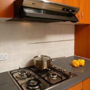 A view of a kitchen, wooden cabinetry, grey countertop, floor, flooring, gas stove, home appliance, kitchen, kitchen appliance, kitchen stove, room, tile, under cabinet lighting, brown, gray