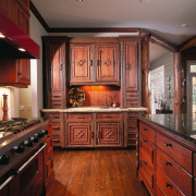 A view of a kitchen, wooden cabinetry and cabinetry, countertop, cuisine classique, flooring, furniture, hardwood, interior design, kitchen, room, wood, wood stain, red