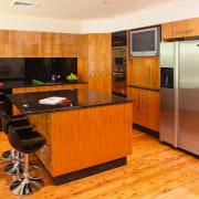 Kitchen with timber veneer, stainless steel appliances, black cabinetry, countertop, floor, flooring, hardwood, interior design, kitchen, laminate flooring, real estate, room, wood flooring, orange