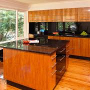 Kitchen with timber veneer, black glass splashback, brown cabinetry, countertop, floor, flooring, hardwood, interior design, kitchen, laminate flooring, real estate, room, wood, wood flooring, wood stain, brown, orange