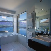 A view of a bathroom, wooden vanity, white bathroom, interior design, real estate, room, window, gray