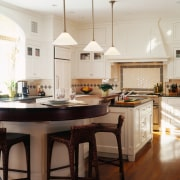 view of the kitchen featuring downlightin, white cabinetry, cabinetry, ceiling, countertop, cuisine classique, dining room, floor, flooring, hardwood, home, interior design, kitchen, laminate flooring, room, wood flooring, white