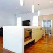 Contemporary kitchen with white cabinetry, and underbench appliances. architecture, floor, flooring, hardwood, home, interior design, kitchen, laminate flooring, real estate, room, wood, wood flooring, white, brown
